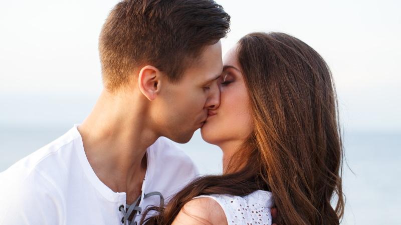 Frau küsst attraktiven Mann