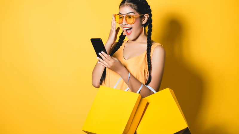 Lustige Frau mit Einkaufstüten und Smartphone