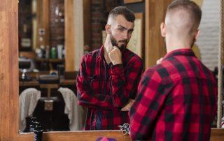Mann vorm Spiegel prüft Outfit fürs Date