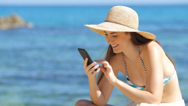 Frau mit Smartphone am Strand liest Tinder-Bio