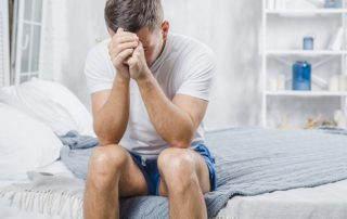 Unglücklicher Single-Mann sitzt auf dem Bett